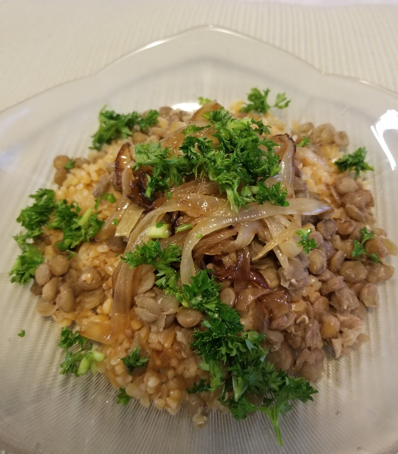 mjadarah a Mediterranean bulgur main dish made of bulgur, lentils, fried onions and garnished with parsley